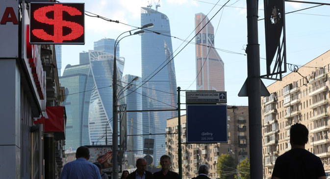 Skyscrapers of the Moscow City business district stand beyond a foreign currency exchange bureau displaying a U.S. dollar sign in Moscow. Source: Getty Images