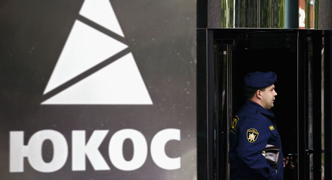 A security guard stands outside the main office building of Russian oil giant Yukos, on July 5, 2004 in Moscow. Source: Getty Images / Fotobank
