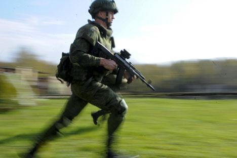 Seorang tentara mengenakan seragam tempur 'Ratnik' dengan menenteng Kalashnikov AK-12 di area tembak.