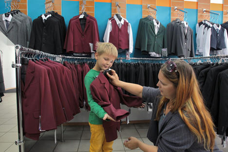 Children and their parents choose a new school uniform. Source: Petr Kovalev / TASS