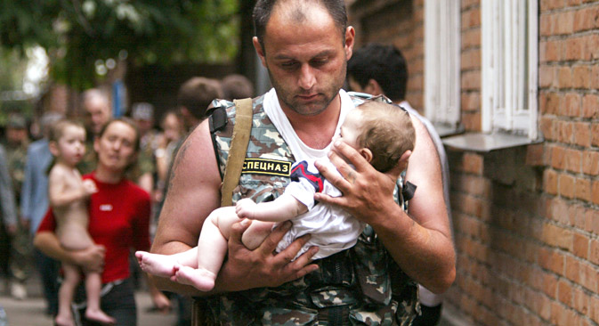 A Russian police officer carries a released baby from a school seized by heavily armed masked men and women in the town of Beslan, 2004. Source: Reuters
