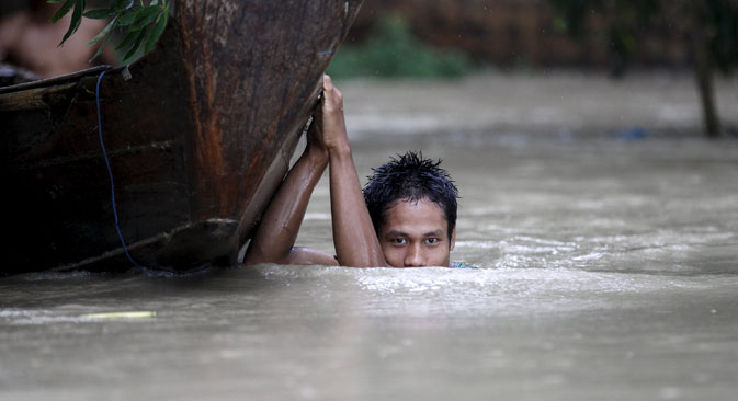 A boy moves his boat in a flooded village outside Zalun Township, Irrawaddy Delta, Myanmar, August 6, 2015. Source: Reuters