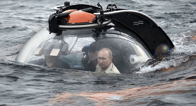 Russian President Vladimir Putin (R) looks through a window of a research bathyscaphe while submerging into the waters of the Black Sea as he takes part in an expedition near Sevastopol, Crimea, August 18, 2015. Source: RIA Novosti/ Kremlin