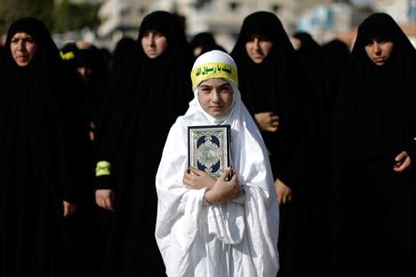 Una chica libanesa sostiene una copia del Corán en una protesta en Líbano. Fuente: AP.