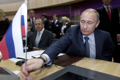 Vladímir Putin con Serguéi Lavrov (al fondo), ministro de Asuntos Exteriores de Rusia. Fuente: ITAR-TASS.