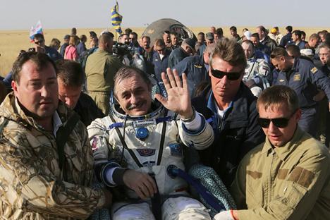 El personal de tierra de la Agencia Espacial rusa lleva en brazos a Pável Vinogradov (centro), Alexander Misurkin (detrás a la derecha) y al estadounidense Chris Cassidy (detrás a la izquierda) poco después de aterrizar en la nave Soyuz a unos 146 kilómetros del pueblo de Zhezkazgan, Kazajistán. Fuente: Reuters