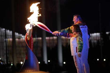 Vladislav Tretyak, presidente de la Federación rusa de hockey sobre hielo, e Irina Rodnina, diputada y tres veces campeona olímpica en patinaje artístico, encienden el pebetero olímpico durante la ceremonia de inauguración de los XXII Juegos Olímpicos de invierno en Sochi. Fuente: Ria Novosti