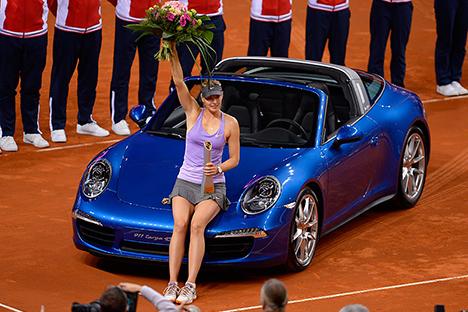 María Sharápova posa con el Porsche 911 Targa 4S que le entregaron tras ganar el torneo de Stuttgart. Fuente: Daniel Maurer/AP Photo