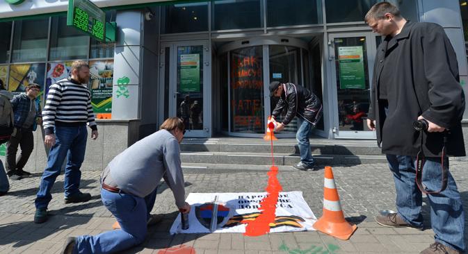 """""""Este banco financia el terrorismo"""", reza la pintada a la entrada del banco Sberbank, mientras varios activistas vierten pintura sobre un cartel. Fuente: AFP / East News"""