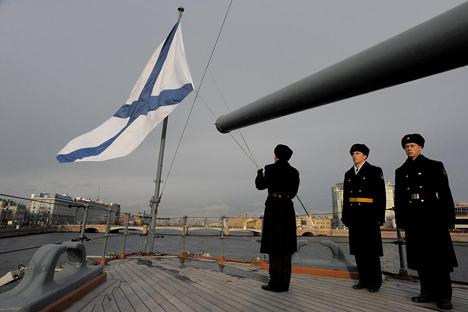 Un miembro de la marina rusa coloca la bandera a media asta en conmemoración del final de la Primera Guerra Mundial en el crucero Aurora, situado en San Petersburgo. Fuente: AFP / East News
