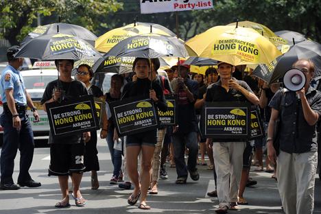 Activistas filipinos, llevando paraguas con eslóganes pintados, se dirigen hacia la oficina consular china para mostrar apoyo a los manifestantes pro democracia en Hong Kong, en una marcha en el distrito financiero de Manila, el 2 de octubre de 2014. Fuente: AFP / East NEws Kommersant.