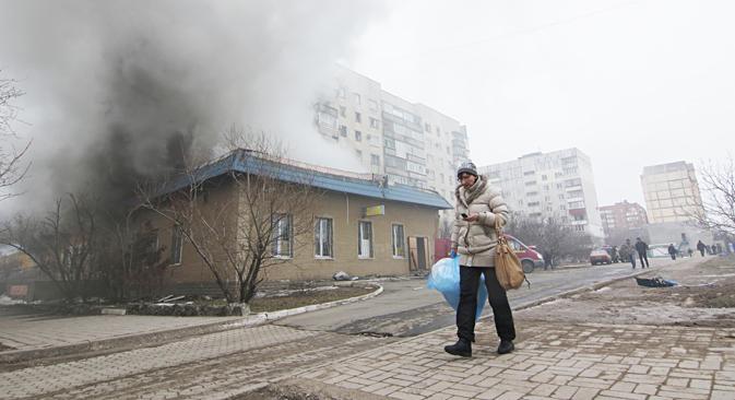 Residente de Mariúpol pasa junto a una casa en llamas durante el ataque producido el pasado sábado, 24 de enero. Fuente: AP