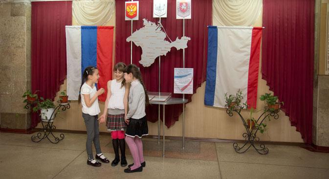 Escolares en una escuela de Crimea ante las banderas de Rusia y la península. Fuente: RIA Novosti.