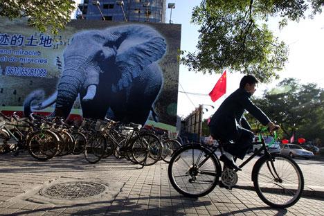 Hombre en bicicleta pasa frente a un cartel de la cumbre China-África celebrada en Pekín en 2006.