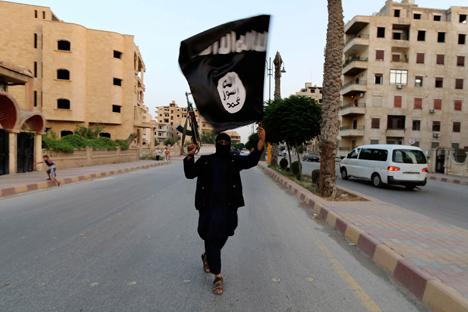 Hombre con bandera del Estado Islámico en Raqqa, Siria. Fuente: Reuters.