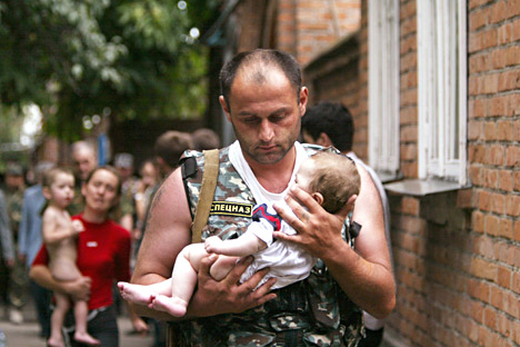 Oficial de policía con un bebé que estaba secuestrado por los terroristas en el ataque a la escuela de Beslán.