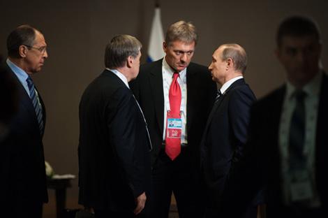 El presidente ruso conversa con su jefe de prensa, Dmitri Peskov (en el centro) y el ministro de Exteriores Serguéi Lavrov (a la izquierda).