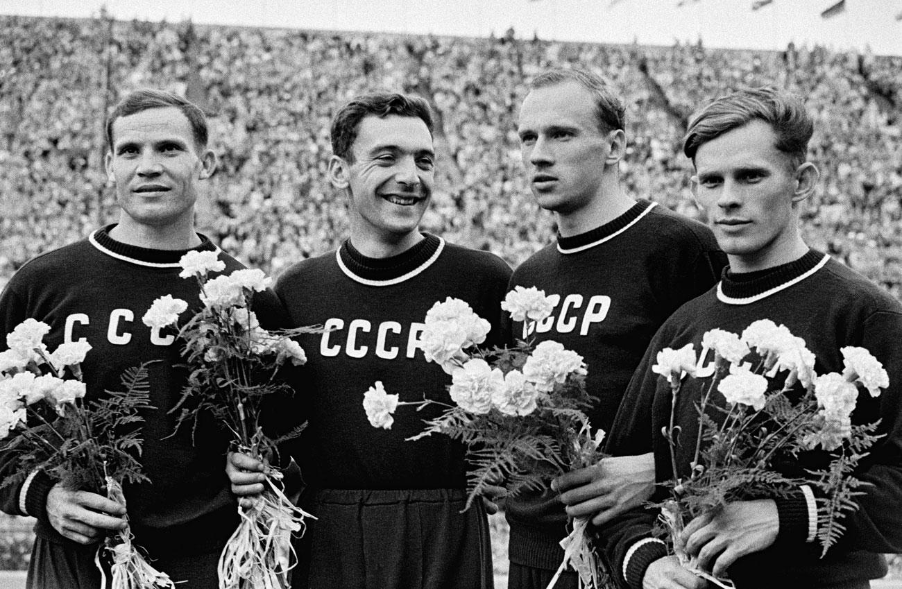 """ХЕЛЗИНКИ 1952 Съветският национален отбор се състезава за първи път н Лятната Олимпиада в Хелзинки през 1952 година. Екипът на отбора е син и се състои от блуза, наподобяваща суитчър, с буквите """"СССР"""", изписани на гърдите. Долната част от екипа е спортен панталон. Именно панталонът (не състезанието) попречва на съветския копиехвъргач Виктор Цибуленко да спечели медал: по време на загрявката той се спъва в крачола си, пада и се контузва. Кремъл незабавно издава заповед панталоните да бъдат стеснени."""