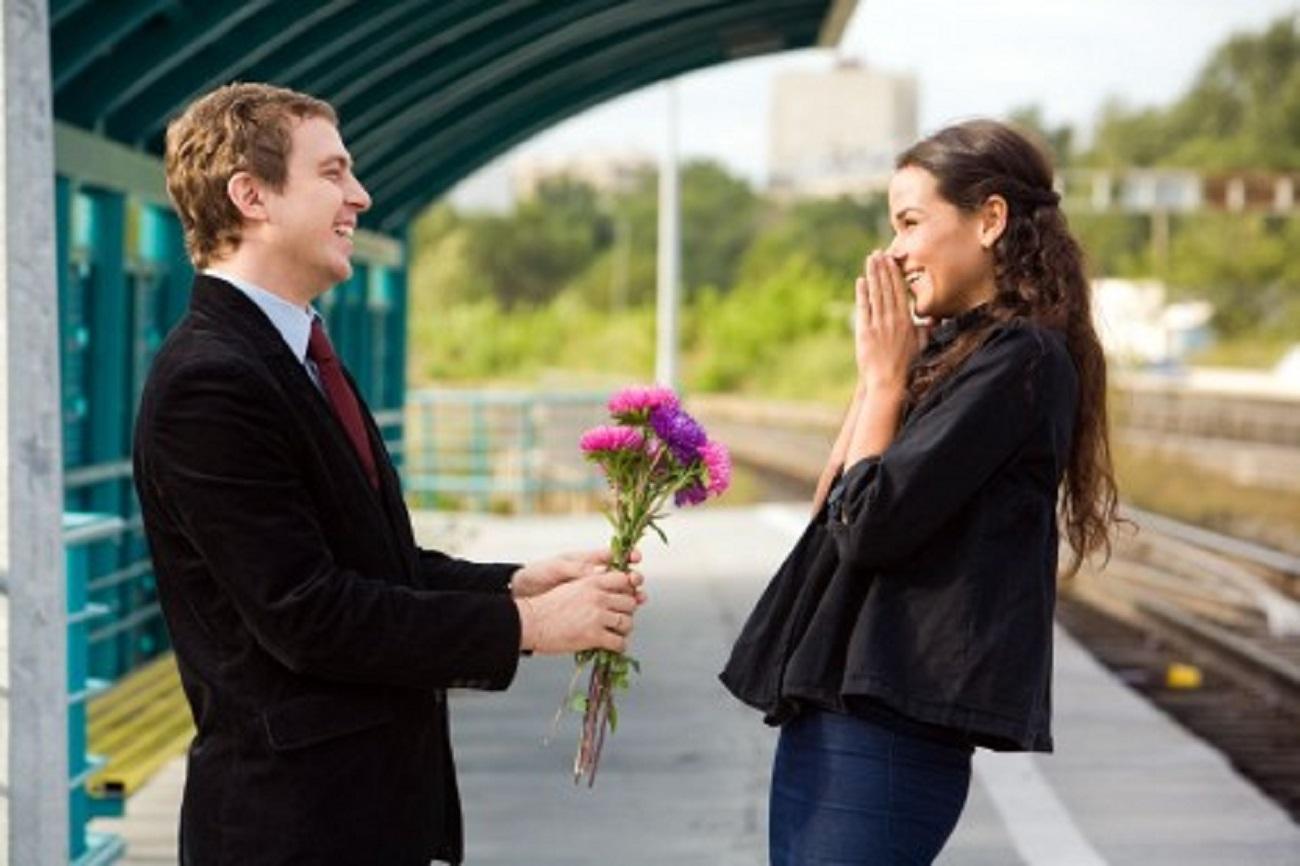 Un hombre sorprende a una mujer con un ramo de flores. Fuente: Panthermedia/Vostock-photo