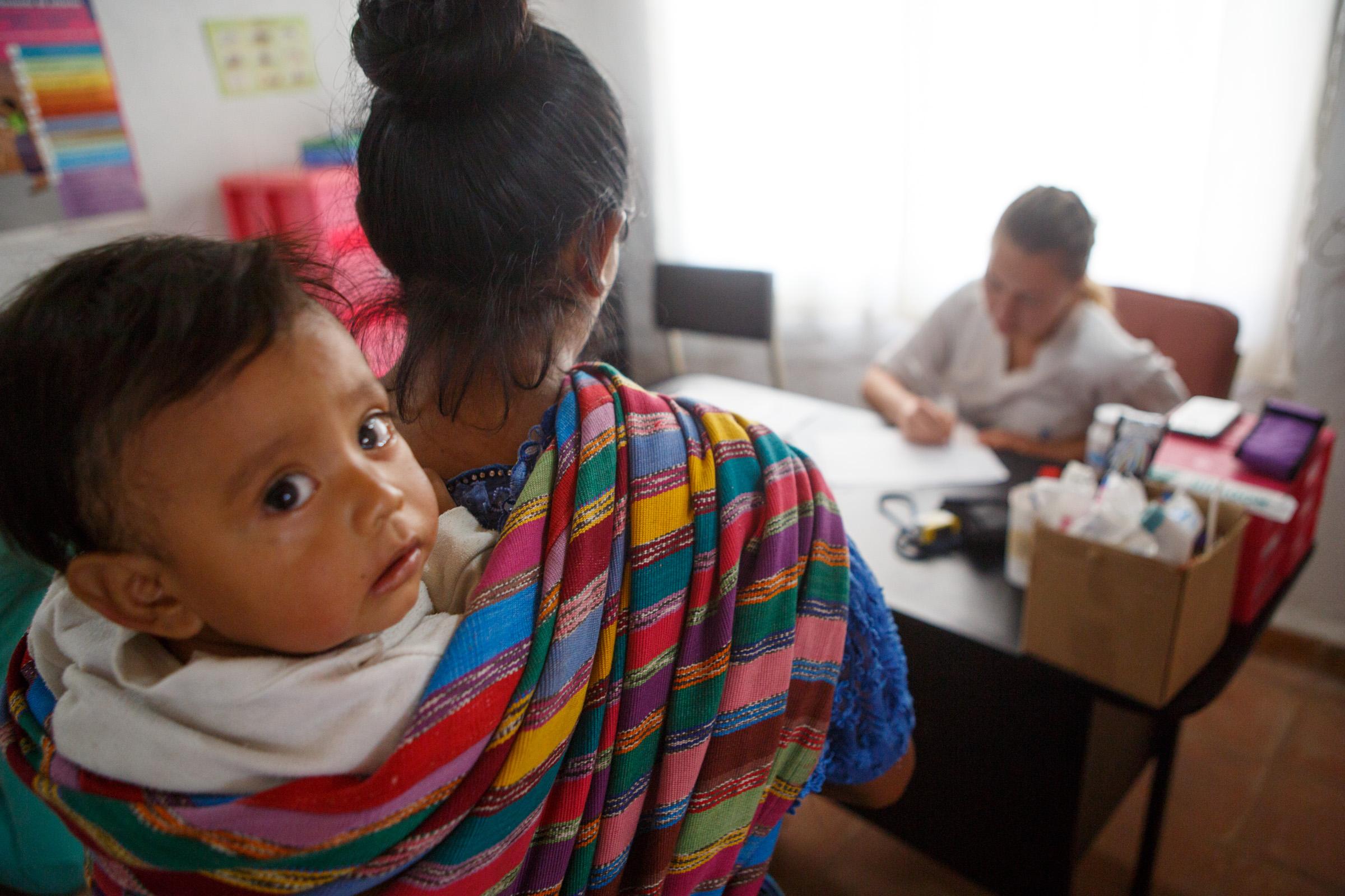 La doctora Victoria Válikova recibe a una madre con el bebé en la clínica.