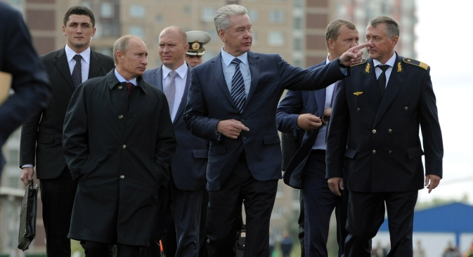 De g. à dr.: Le président russe Vladimir Poutine, le maire de Moscou Sergueï Sobianine et le directeur du métro de Moscou Ivan Bessedine examinent la nouvelle station du métro Novokossino. Crédit : AP/Alexeï Droujinine