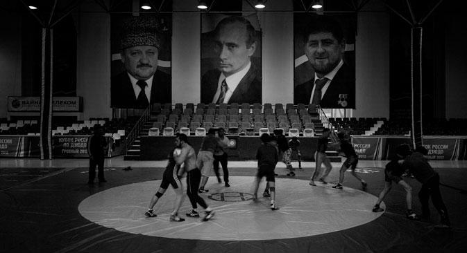 Entraînement de lutte dans un gymnase. Les portraits en arrière-plan de gauche à droite représentent : Akhmad Kadyrov, Vladimir Poutine et Ramzan Kadyrov. Crédit photo : Davide Monteleone