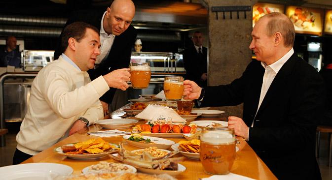 Le premier ministre russe Dmitri Medvedev (à gauche) et le président russe Vladimir Poutine boivent de la bière au bar Jigouli, dans le centre de Moscou. Crédit : Itar-Tass