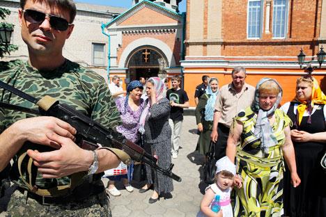 Un rebelle armé se tient près de croyants orthodoxes locaux sortant de la cathédrale Alexandre Nevski, après une messe dominicale dans la ville ukrainienne de Slaviansk, le 18 mai 2014. Crédit : Reuters