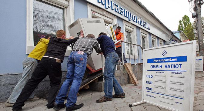 Les ouvriers sortent le distributeur de billets de la banque Ukrgazprombank. Crédit : Taras Litvinenko/RIA Novosti