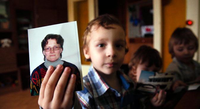 Un enfant de Svetlana Davydova tient la photo de sa mère. Crédit : Reuters