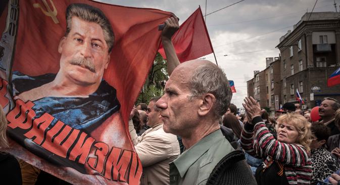 À Donetsk, le 1er mai 2014. Des manifestants avec des drapeaux soviétiques et un portrait de Joseph Staline participent au traditionnel défilé du 1er mai. Sergey Ponomarev pour New York Times