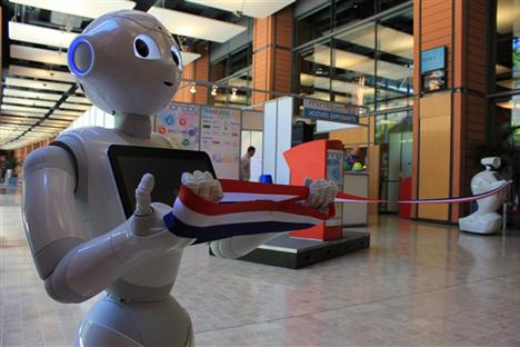 """Les robots japonais Pepper et russe Promobot (à droite) """"inaugurent"""" l'exposition INNOROBO 2015. Crédit : Skolkovo Robotics Center"""