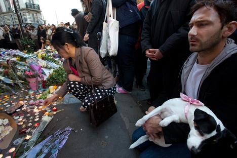 Des Français rendent hommage aux victimes des attentats parisiens sur les lieux d'attaques près du restaurant Le Petit Cambodge et le bistrot Le Carillon le 15 novembre 2015.