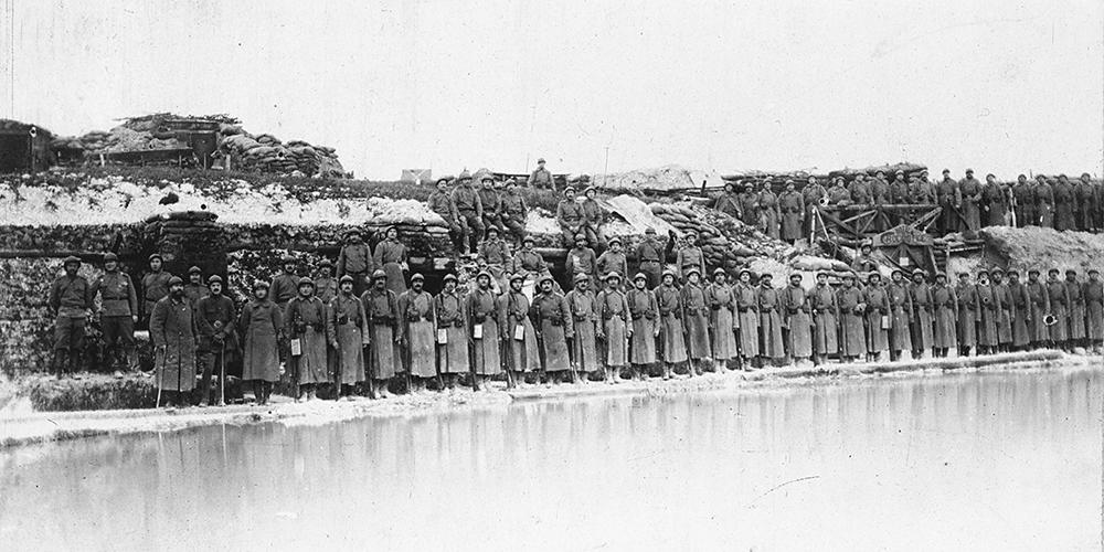 L'hiver 1916-17, une compagnie alignée devant ses positions, on remarque les cheminées des abris, avec un petit lac gelé qui s'est formé.