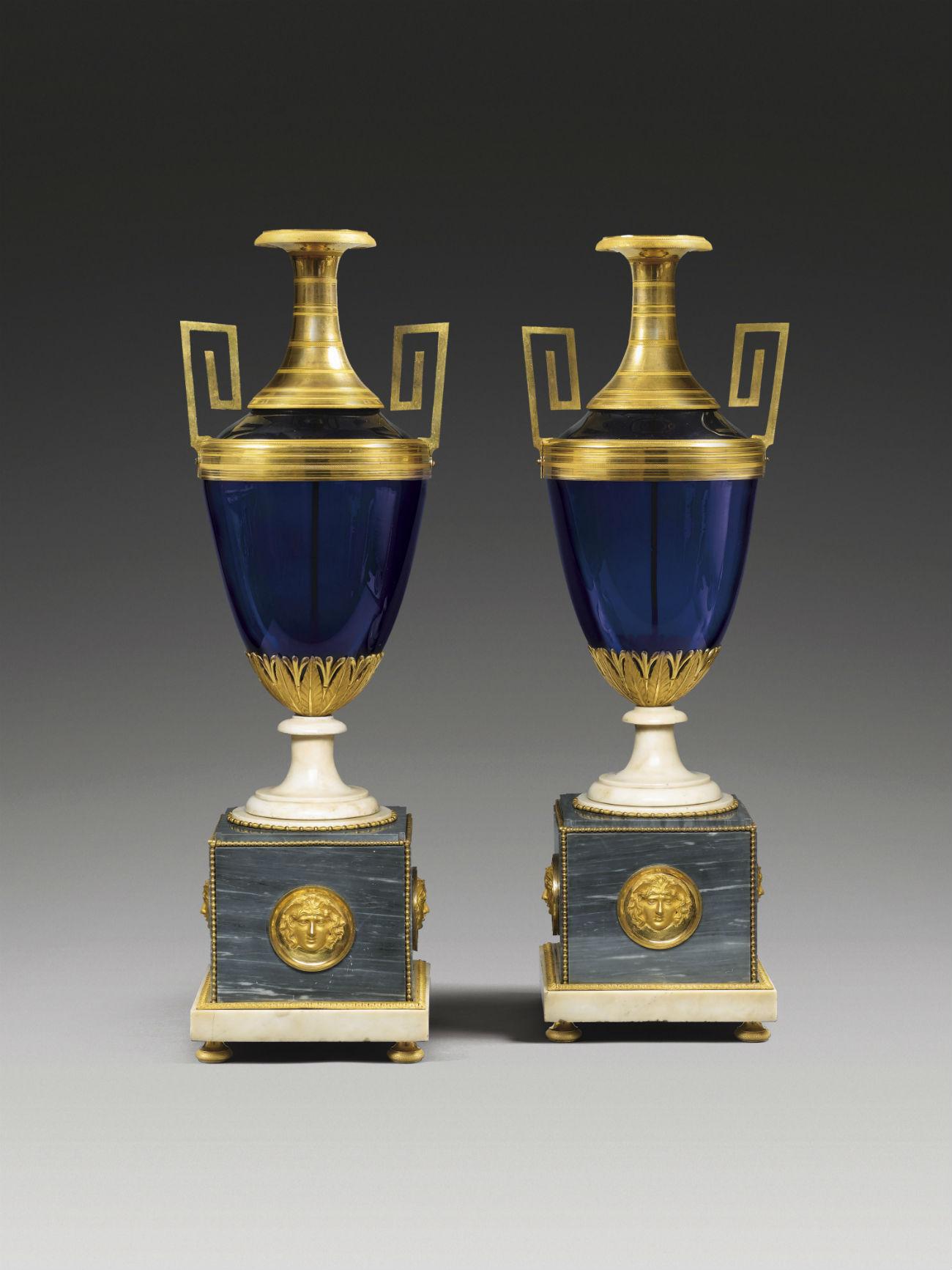 Deux vases en verre bleu, garnis d'éléments plaqués or et montés sur pied de marbre. Crédit : Galerie Perrin