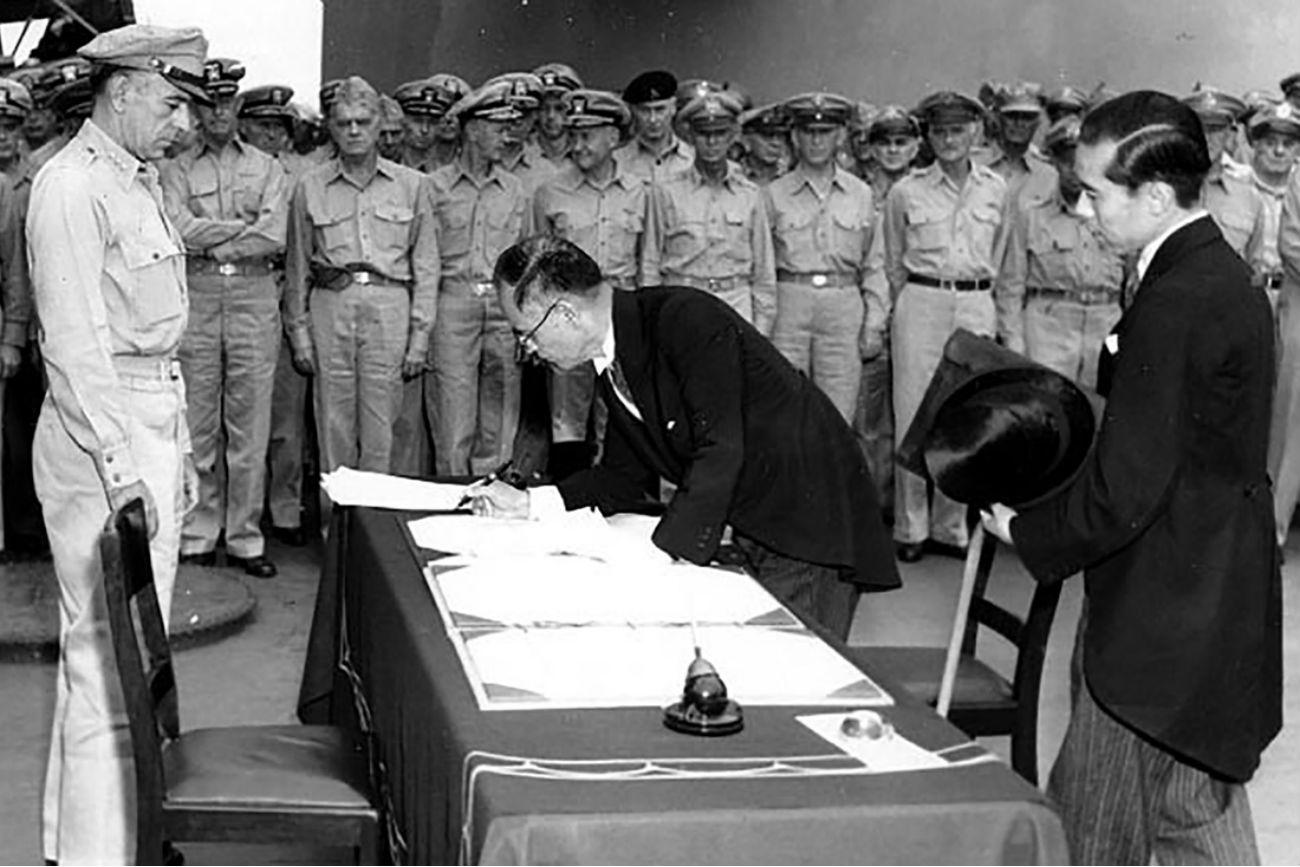 Japonski zunanji minister Mamoru Šigemitsu podpisuje dokument o predaji japonske na ladji USS Missouri. Opazuje ga general Richard K. Sutherland. 2. september 1945.