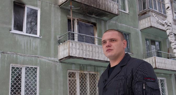 """Aleksandar Okonječnikov, taksist iz sibirskog grada Tomska, stoji ispred zgrade u Ulici Internacionale 31. On je upravo ovdje uspio kroz prozor spasiti četvero djece kada je u njihovom stanu na prvom katu izbio požar. Izvor: RIA """"Novosti""""."""