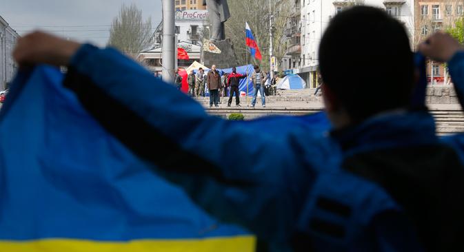 Proukrajinski pristaše stoje s ukrajinskom zastavom nasuprot proruskih pristaša u Donjecku, u istočnoj Ukrajini. Izvor: AP