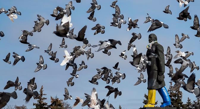 Jato golubova u Kramatorsku leti oko spomenika osnivaču Sovjetskog Saveza Vladimiru Lenjinu, obojanog u boje ukrajinske zastave. Izvor: Reuters
