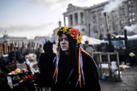 Seorang warga di Kiev mensurvei keadaan pascakonfrontasi di Maidan. Kredit: AFP/East News