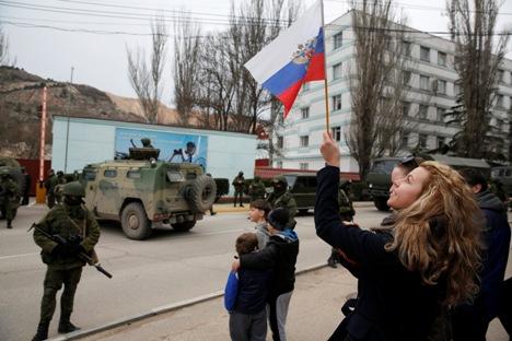 Seorang wanita mengibarkan bendera Rusia sementara para tentara bersenjata berjaga di dekat kendaraan militer Rusia di luar pos perbatasan kota Balaclava, Krimea, 1 Maret 2014. Kredit: Reuters