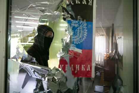 Seorang pria bertopeng berjalan melewati jendela yang pecah dari di dalam balai kota Mariupol di timur Ukraina, 26 April 2014. Foto: Reuters
