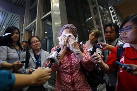 Jurnalis televisi mencoba mewawancarai seorang ibu yang tengah menangis menunggu kepastian kabar mengenai pesawat Malaysia Airlines MH17 yang ditembak jatuh di Ukraina. Foto: Reuters