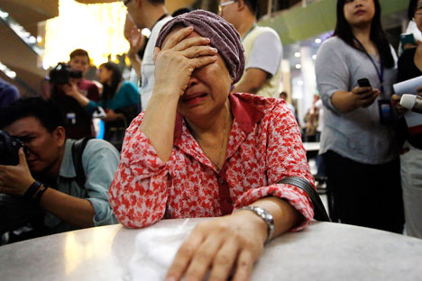 Seorang ibu menangis di Bandar Udara Internasional Kuala Lumpur seraya menunggu informasi mengenai jatuhnya peswat. Foto: Reuters