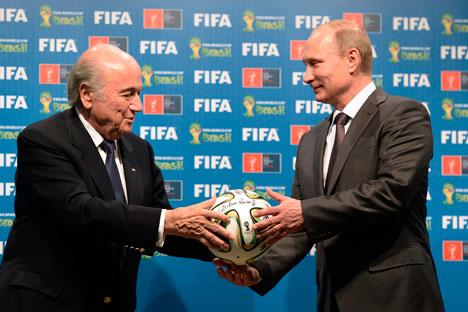 Presiden FIFA Sepp Blatter menyerahkan bola kepada Presiden Rusia Vladimir Putin sebagai simbol serah terima penyelenggaraan Piala Dunia 2018 di Rusia. Foto: AP