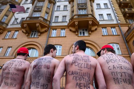 """""""Sanksi terhadap Rusia adalah sanksi terhadap saya!"""" Orang-orang bepartisipasi dalam unjuk rasa di luar kedutaan besar AS di Moskow pada awal Maret lalu, ketika sanksi pertama terhadap Rusia diberlakukan. Foto: Evgeny Biyatov/RIA Novosti"""
