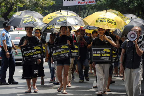 Para aktivis Filipina membawa payung yang bertuliskan slogan-slogan dan berbaris menuju kantor konsulat Tiongkok untuk menunjukkan dukungan mereka pada demonstran pro-demokrasi Hong Kong selama unjuk rasa di Manila, 2 Oktober 2014. Foto: AFP/EastNews
