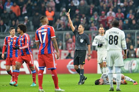 Pemain Bayern, Dante dari Brasil (kedua dari kiri), dihentikan wasit Olegario Benquerenca setelah melakukan pelanggaran terhadap pemain CSKA Alan Dzagoe (kanan) dalam pertandingan sepak bola grup E Liga Champions antara FC Bayern Munich dan CSKA Moscow di Munich, Jerman, (10/12). Foto: AP