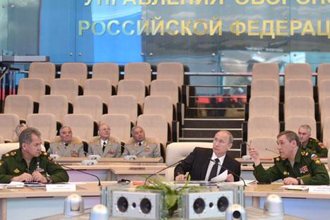 Prasiden Rusia Vladimir Putin (tengah), Menteri Pertahanan Rusia Sergey Shoigu (kiri), dan Kepala Staf Umum Angkatan Bersenjata Rusia Valery Gerasimov (kanan) di Pusat Manajemen Pertahanan Nasional. Foto: Alexey Nikolsky/RIA Novosti