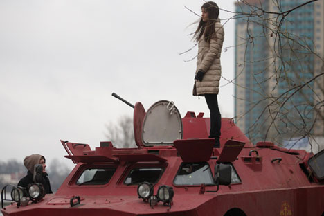 Tampilan luar taksi tank berwarna merah terang dengan logo perusahaan terlihat di bagian depan dan samping. Kredit: Igor Russak/Ria Novosti